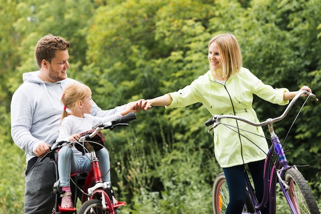 Family on bicycles holding hands Free Photo