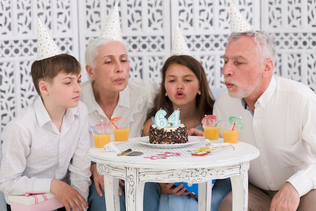 Family blowing number candles on birthday cake with glasses of juice on table Free Photo