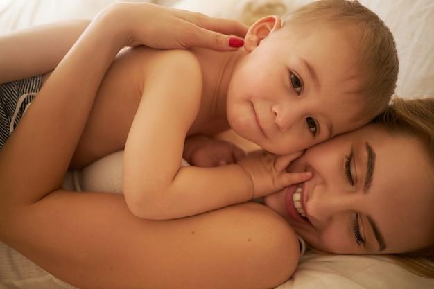 Legami familiari e concetto di maternità. immagine ritagliata di bella giovane mamma europea rilassante in camera da letto sdraiato su lenzuola bianche con il suo adorabile figlio bambino, tenendolo stretto e sorridendo felicemente Foto Gratuite