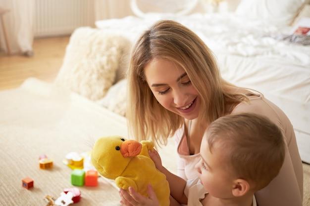 家族、子供時代、母性およびふりの概念。ぬいぐるみの黄色いアヒルと遊ぶおもちゃに囲まれた愛らしい赤ちゃんの息子と一緒に寝室の床に座っている金髪の若いお母さんのかわいいシーン 無料写真