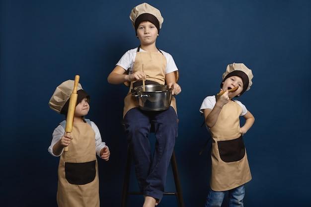 가족, 어린이 및 요리 개념. 요리사 유니폼을 입고 포즈를 취하는 세 백인 아이 형제의 절연 스튜디오 초상화, 다양한 주방 용품을 들고 함께 수프를 준비하거나 피자를 만들기 무료 사진
