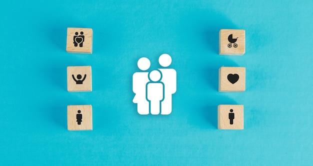 木製のブロック、青いテーブルフラットの紙家族アイコンと家族の概念を置きます。 無料写真