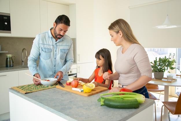 Famiglia che cucina la cena a casa durante la pandemia. coppia giovane e capretto tagliare le verdure per insalata al tavolo della cucina. una sana alimentazione o mangiare a casa concetto Foto Gratuite