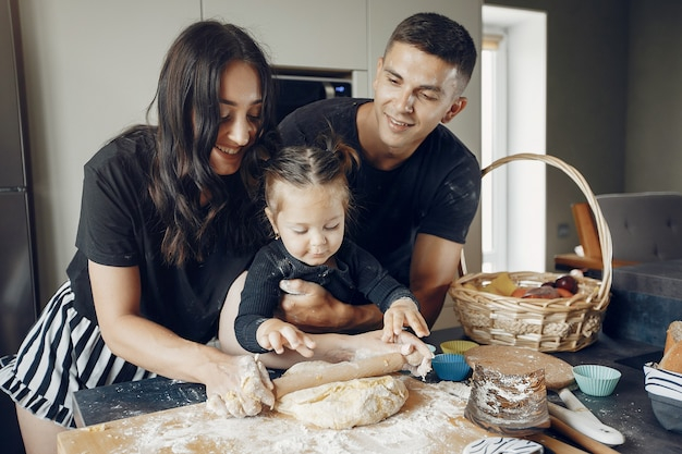 Family cooks the dough for cookies at the kitchen Free Photo