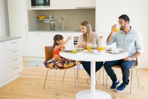 家族カップルとキッチンで一緒に朝食を持っていること、ダイニングテーブルに座っていること、オレンジジュースを飲むことと話している女の子。 無料写真