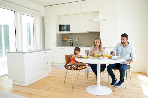 家族のカップルと子供が一緒にキッチンで朝食をとり、皿とオレンジジュースのダイニングテーブルに座って 無料写真