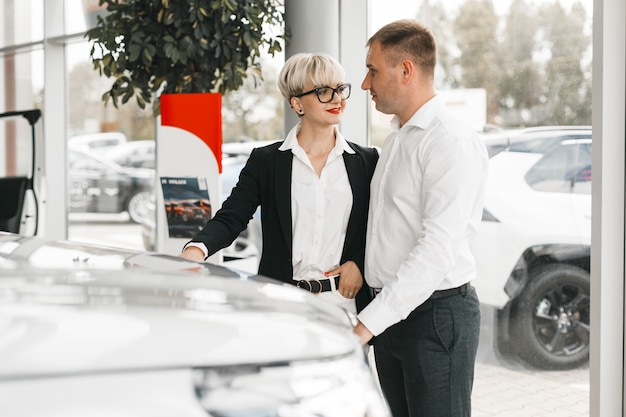 Family couple choose a car in dealership standing and looking each other. . Premium Photo