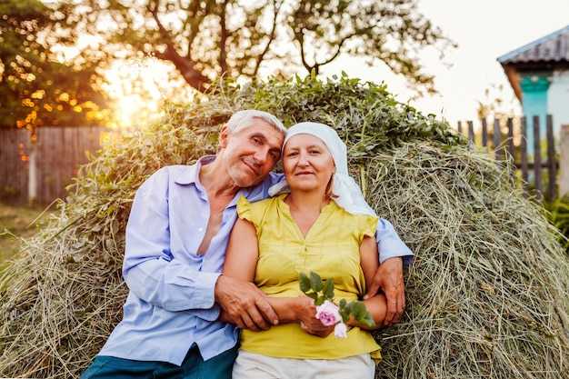 Family couple of farmers sitting on haystack and relaxing at sunset in countryside. Premium Photo