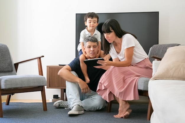 a couple and their son looking at a ipad screen on the living room