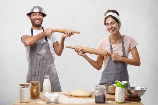 Семейная пара дурачится на кухне, стреляет друг в друга скалкой Бесплатные Фотографии