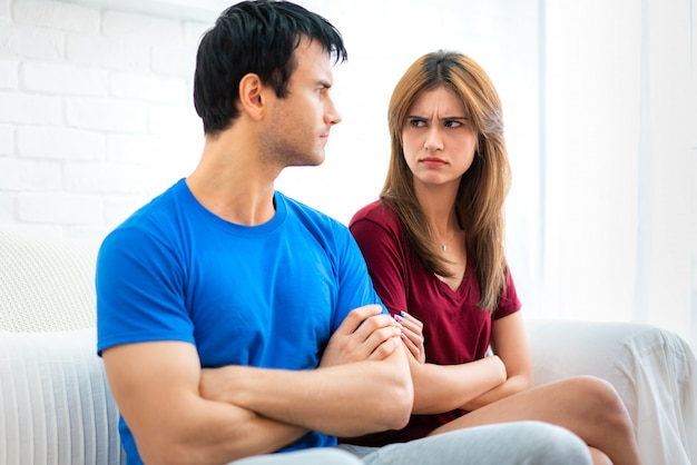 Family couple sitting on the couch not talking after argument, young husband is tired of constant quarrelling offended woman turned her back to boyfriend with arms across. Premium Photo