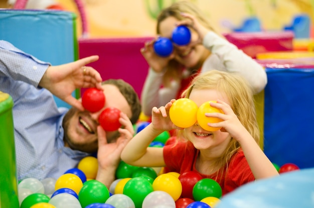Family covering eyes with balls Free Photo