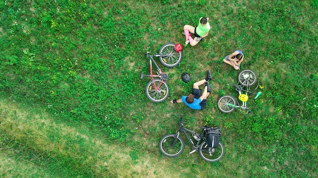 Family cycling on bikes aerial view from above, happy active parents with child have fun and relax on grass, family sport and fitness on weekend Premium Photo