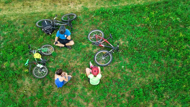Family cycling on bikes aerial view from above, happy active parents with child have fun Premium Photo