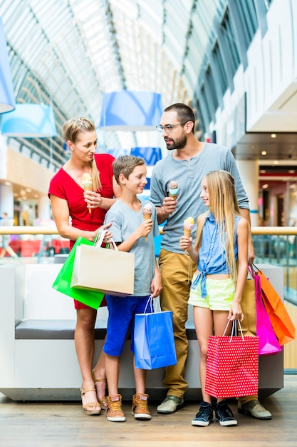 Family eating ice cream in shopping mall with bags Premium Photo