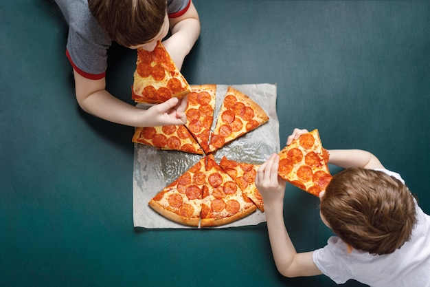 Family eating peperoni pizza. kids holding a slice of pizza. Premium Photo