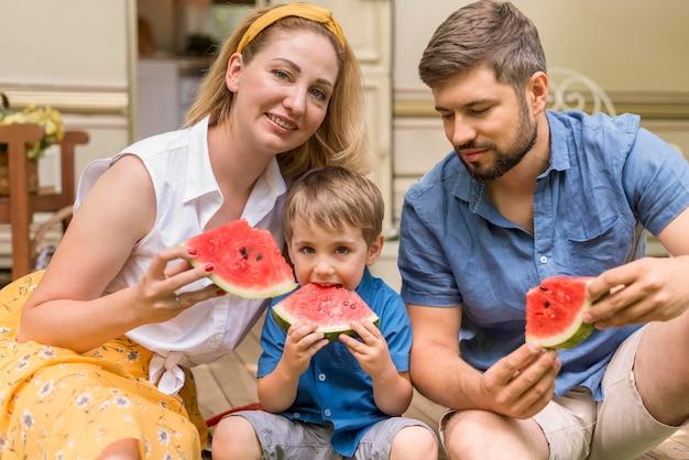 キャラバンの横にあるスイカを一緒に食べる家族 無料写真