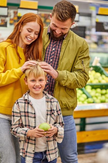 가족은 캐주얼 의류에 귀여운 꼬마 소년과 슈퍼마켓 통로에있는 어린 부모, 아이 소년과 함께 쇼핑을 즐기고 재미를 느낍니다. 프리미엄 사진