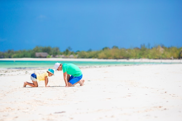 Family of father and kid on white sandy beach Premium Photo