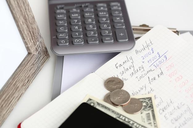 テーブルの上に横たわるメモ帳ページに書かれた家族の財務統計 Premium写真