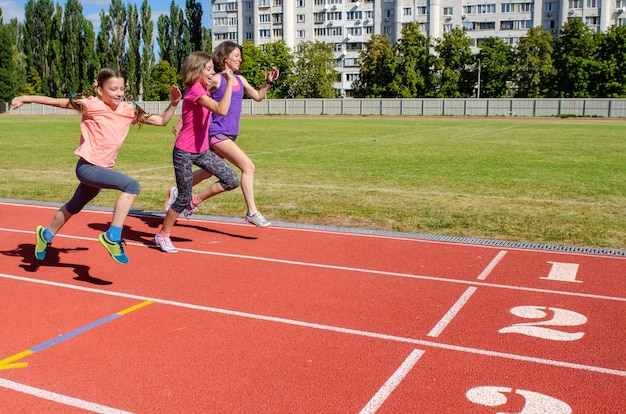Family fitness, mother and kids running on stadium track, exercise with children  and sport healthy lifestyle concept Premium Photo