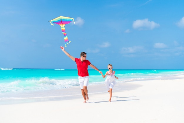 Family flying kite together at tropical white beach Premium Photo