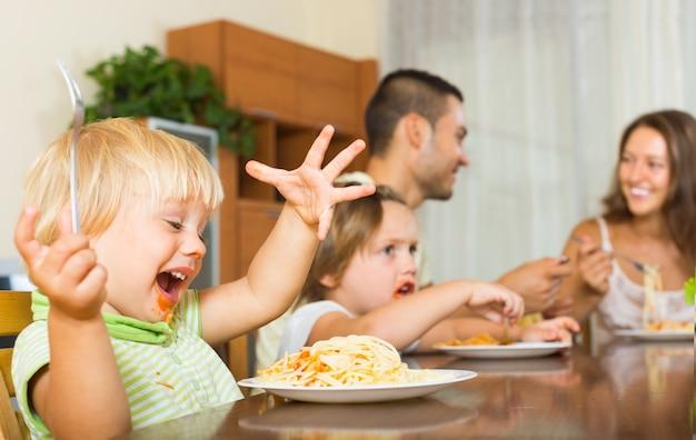 Family of four eating spaghetti Free Photo
