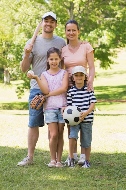 Family of four holding baseball bat and ball in park Premium Photo