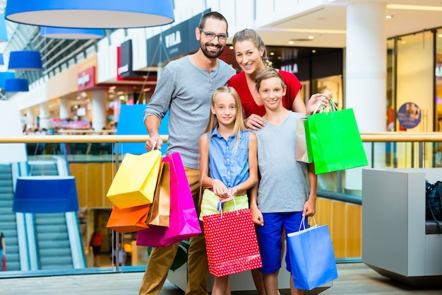 Family of four in shopping mall with bags Premium Photo
