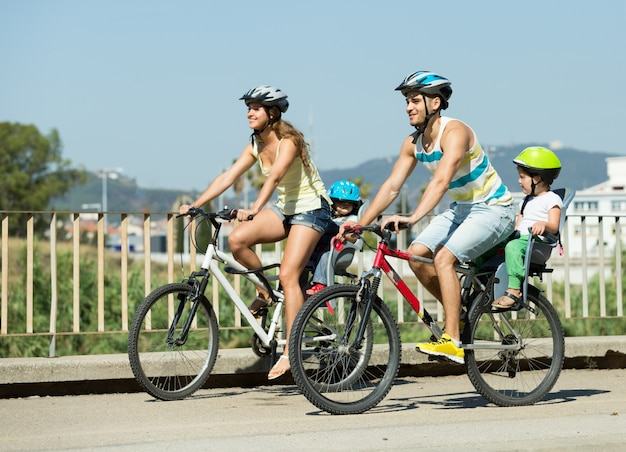 Family of four traveling by bicycles Free Photo