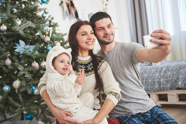 Family gathered around a christmas tree, using a tablet Premium Photo