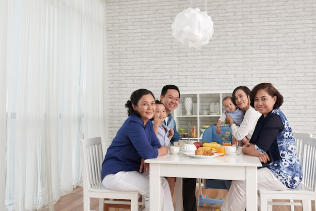 Family gathering at dinner table Free Photo