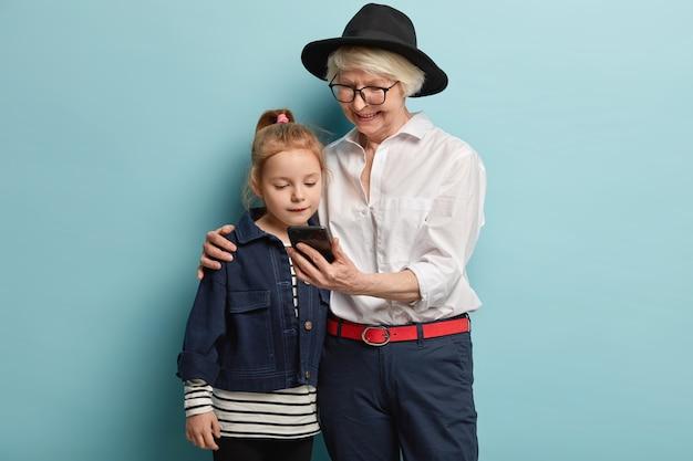 家族、世代、技術の概念。幸せなファッショナブルな祖母はスマートフォンを持って、女性の孫を抱きしめ、一緒にビデオを見て、家で一緒に素敵に過ごし、青い壁を越えてポーズをとる 無料写真