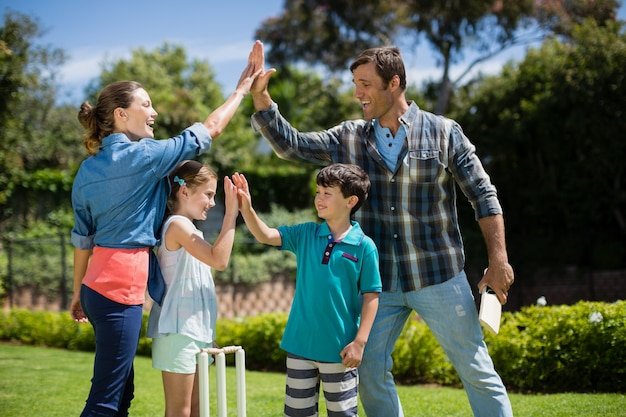 Family giving high five to each other while playing cricket Premium Photo