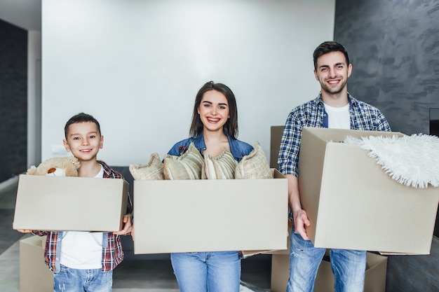 Family go into a new house holding boxes with things Premium Photo