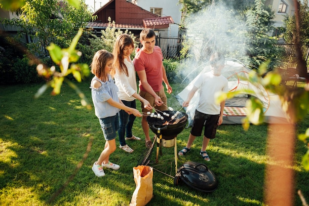 Family grilling marshmallow on barbecue grill at park Free Photo