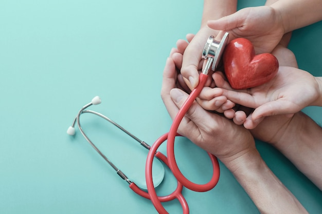 Family hands holding red heart with stethoscope Premium Photo