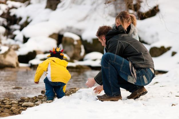 Family having winter walk at river Premium Photo
