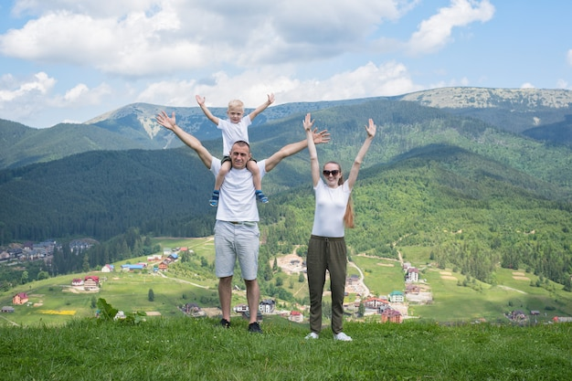 Семейный отдых. родители с маленьким сыном встают с поднятыми руками. горы на заднем плане. Premium Фотографии