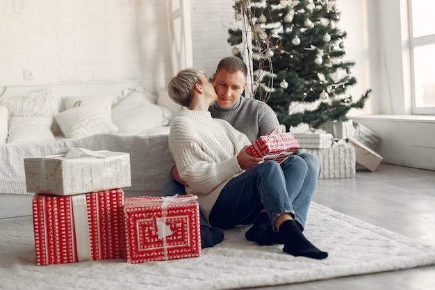 Famiglia a casa. coppia vicino a decorazioni natalizie. donna in un maglione grigio. Foto Gratuite