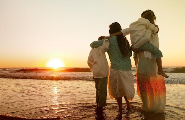 Famiglia che si abbraccia mentre si trova sulla spiaggia circondata dal mare durante il tramonto Foto Gratuite