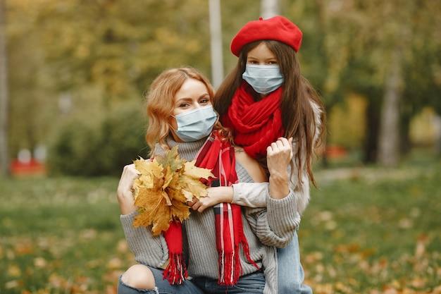秋の公園の家族。コロナウイルスのテーマ。娘と母。 無料写真
