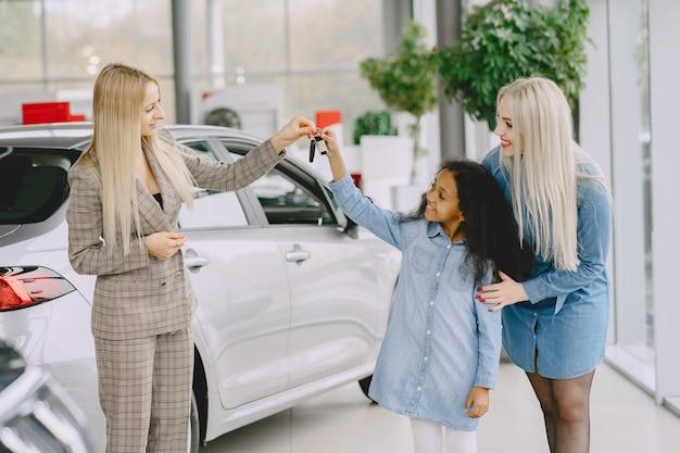 カーサロンの家族。車を買う女性。 mtherと小さなアフリカの女の子。クライアントとのマネージャー。 無料写真