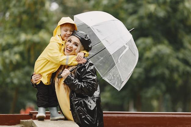 雨の公園の家族。黄色いレインコートを着た子供と黒いコートを着た女性。 無料写真