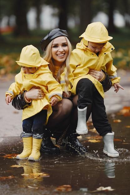 雨の公園の家族。レインコートを着た子供たち。子供を持つ母。黒いコートを着た女性。 無料写真