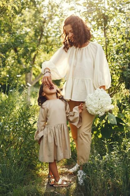 夏の庭で家族。官能的な写真。かわいい女の子。花束を持つ女性。 無料写真