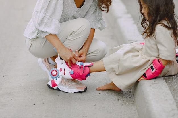 Семья в летнем парке. мать в кофточке. маленькая девочка с роликом. Бесплатные Фотографии