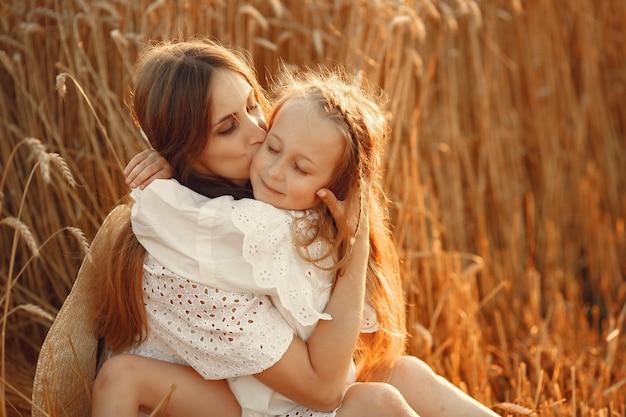 Семья в пшеничном поле. женщина в белом платье. девушка в соломенной шляпе. Бесплатные Фотографии