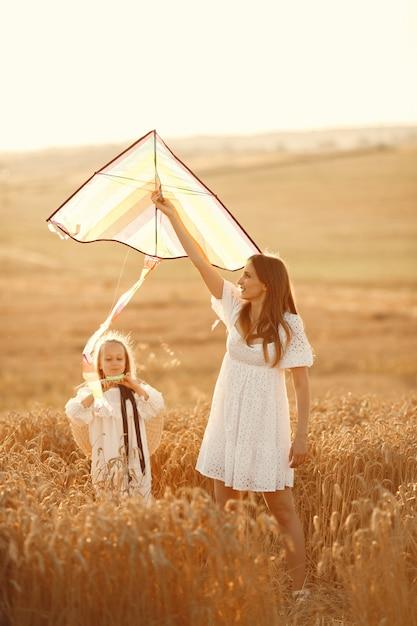 Семья в пшеничном поле. женщина в белом платье. маленький ребенок с воздушным змеем. Бесплатные Фотографии