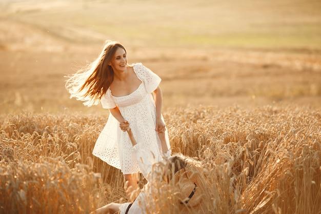 Семья в пшеничном поле. женщина в белом платье. Бесплатные Фотографии